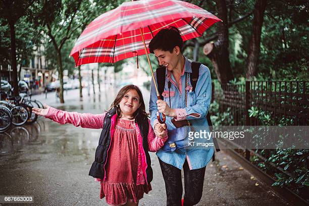 Mother and daughter walking the street in the rain