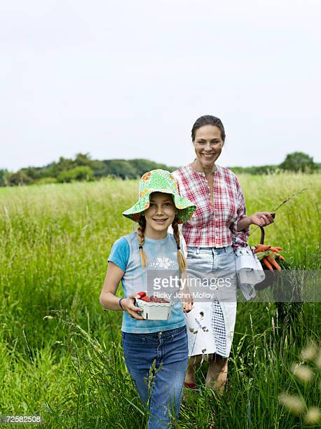 Mother and daughter (10-11) walking through long grass
