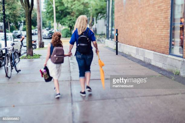Mother and daughter walking to school in city street morning.