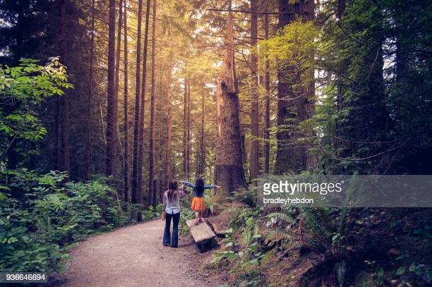 Mother and daughter walking together in Oregon forest