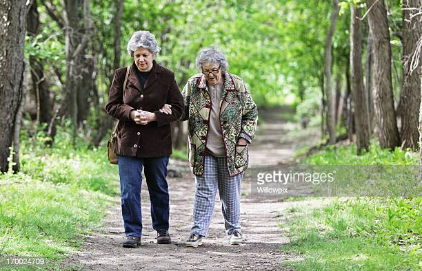 mother and daughter walking together on nature trail - fat granny stock pictures, royalty-free photos & images