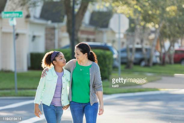 mother and daughter walking together, talking - pre adolescent child stock pictures, royalty-free photos & images