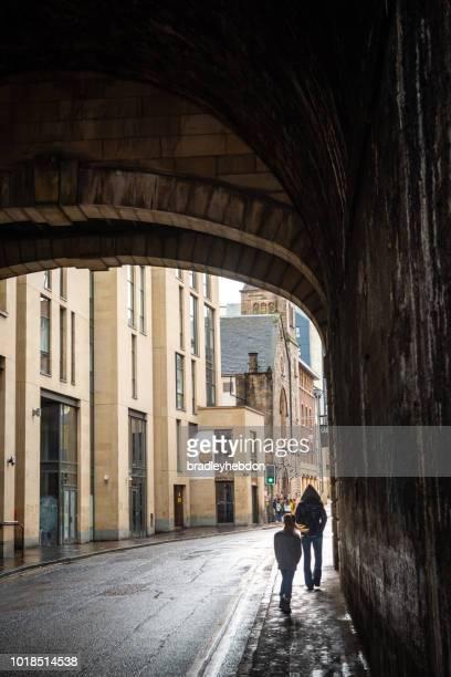 Mother and daughter walking under bridge in Edinburgh, Scotland