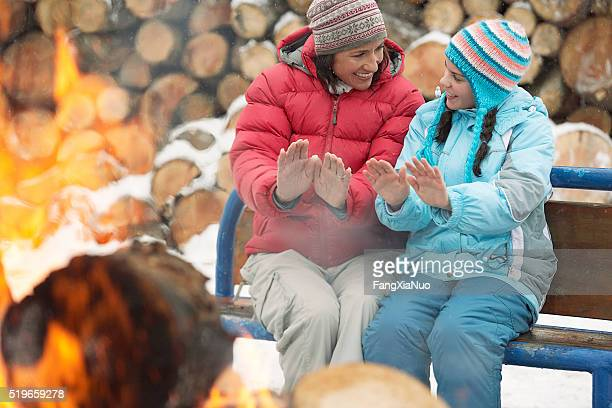Mother and daughter warming hands by fire