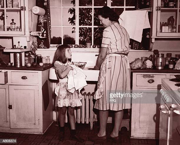 mother and daughter (8-10) washing and wiping dishes (b&w sepia tone) - stay at home mother stock pictures, royalty-free photos & images