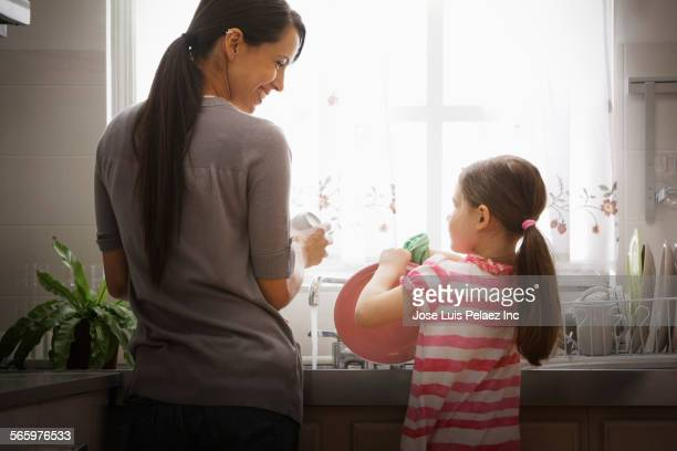 Mother and daughter washing dishes in kitchen