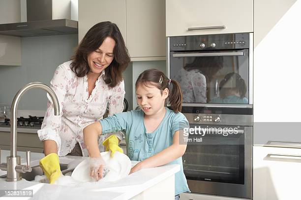 mother and daughter washing dishes - kids with cleaning rubber gloves stock pictures, royalty-free photos & images