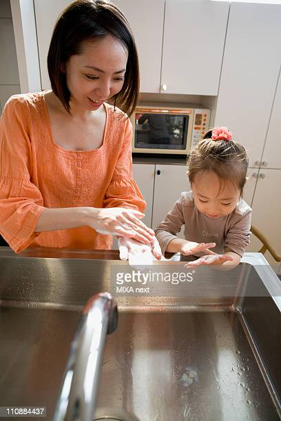 mother and daughter washing hands - 日本人のみ ストックフォトと画像