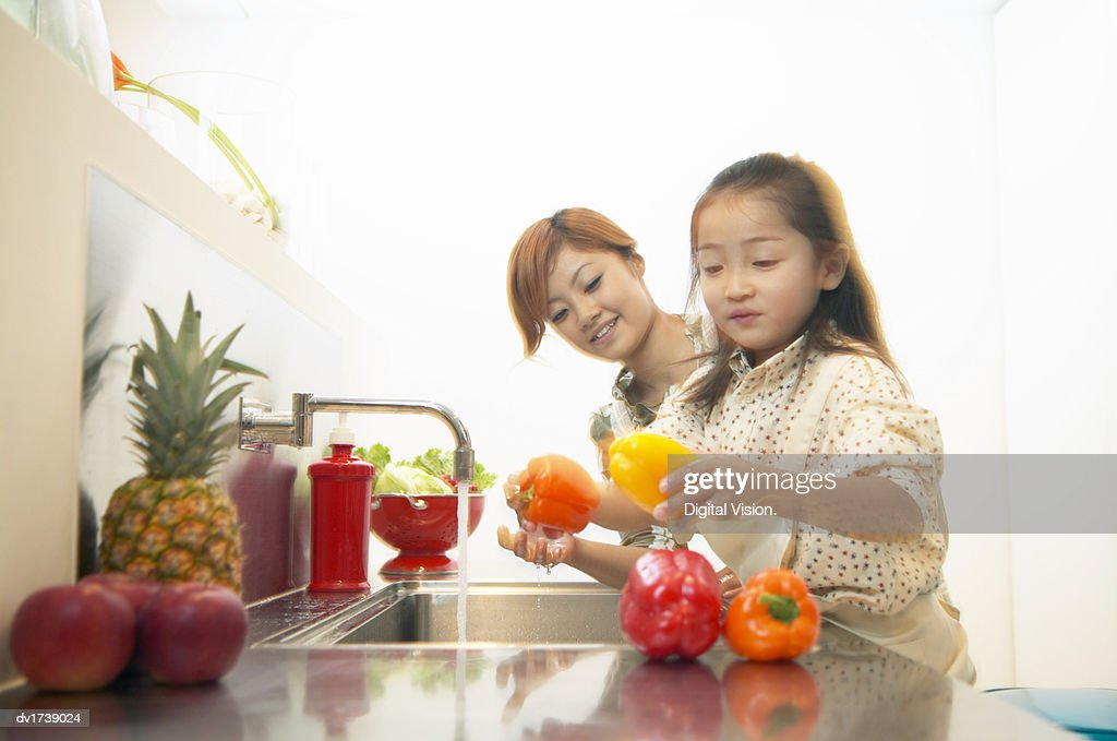 Mother and Daughter Washing Peppers at a Kitchen Sink : Stock Photo