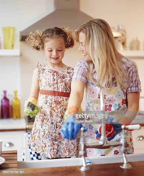 mother and daughter (4-6)  washing-up, smiling - kids with cleaning rubber gloves stock pictures, royalty-free photos & images