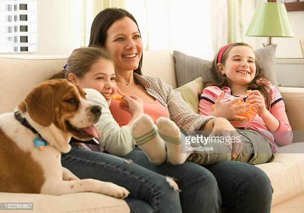 Madre e hija ver televisión con perro de familia
