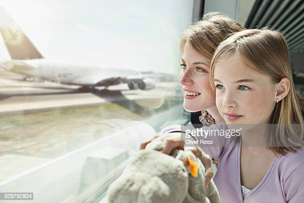 mother and daughter (5-6) watching airplanes at airport - kid in airport stock-fotos und bilder