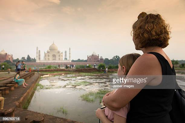 A mother and daughter watching The Taj Mahal at sunset.