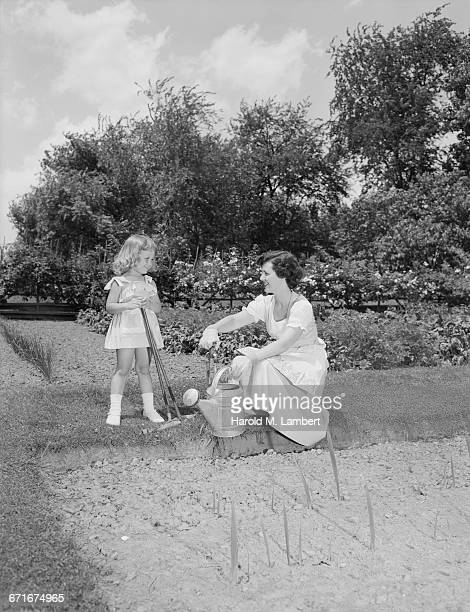 mother and daughter watering their garden - {{relatedsearchurl(carousel.phrase)}} stock pictures, royalty-free photos & images