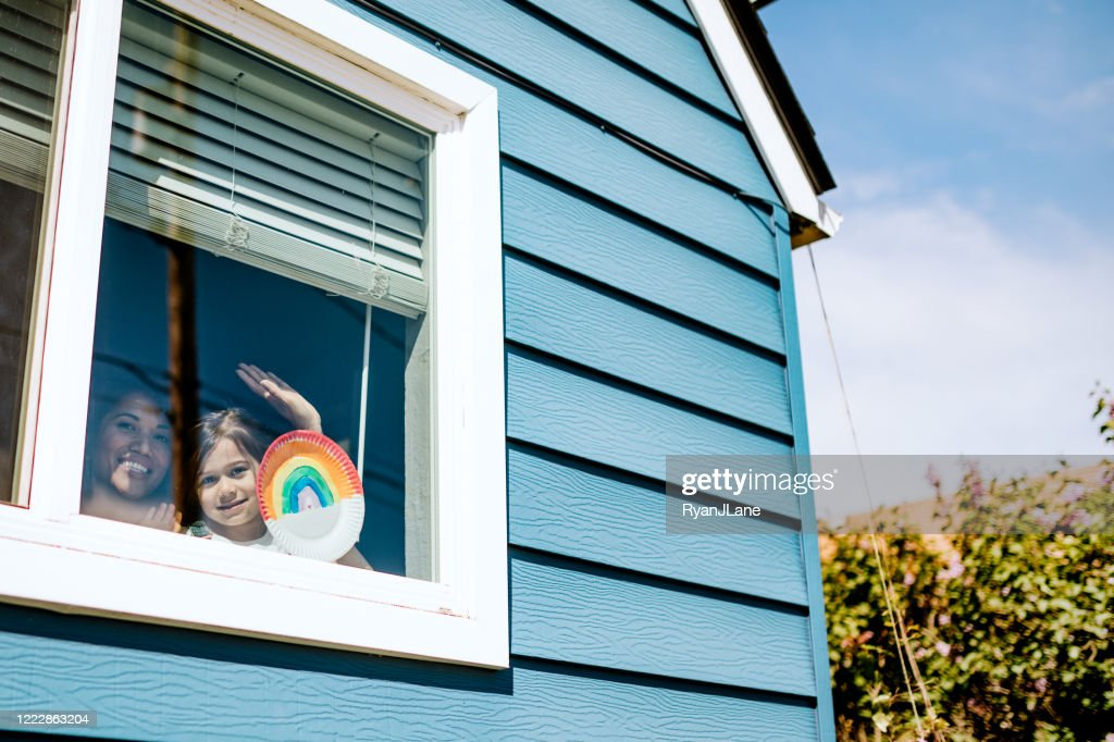Mother And Daughter Wave Out Home Window With Artwork : Stock Photo