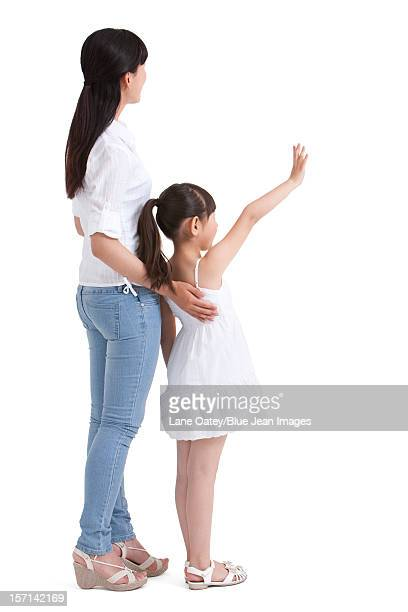 Mother and daughter waving to the front