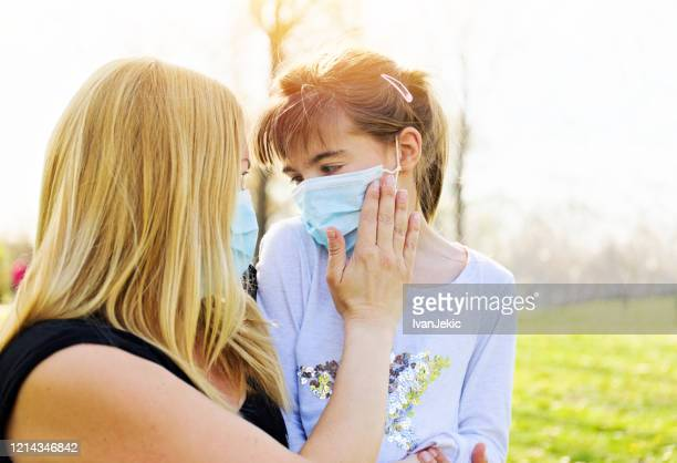 mother and daughter wear a face mask together - ivanjekic stock pictures, royalty-free photos & images