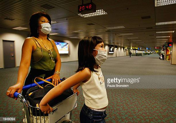 A mother and daughter wear surgical masks as they check the departure time of their flight at Changi International Airport April 24 2003 in Singapore...