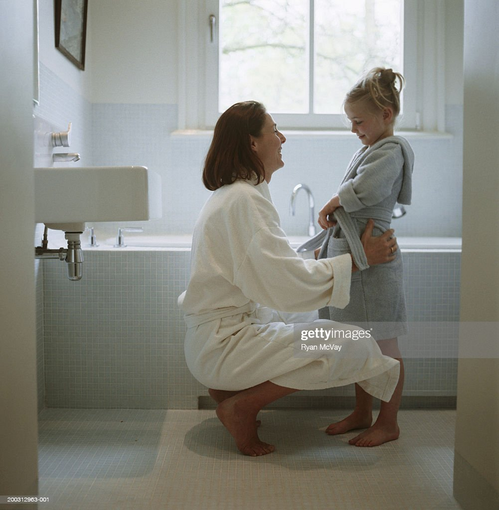 Mother and daughter (2-3) wearing dressing gowns in bathroom : Stock Photo