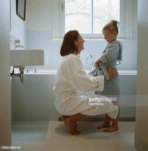 Mother and daughter (2-3) wearing dressing gowns in bathroom