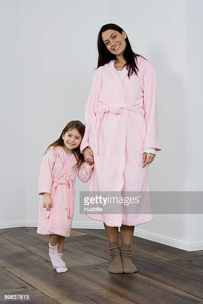 a mother and daughter wearing pink bathrobes holding hands - pink sock image stock pictures, royalty-free photos & images