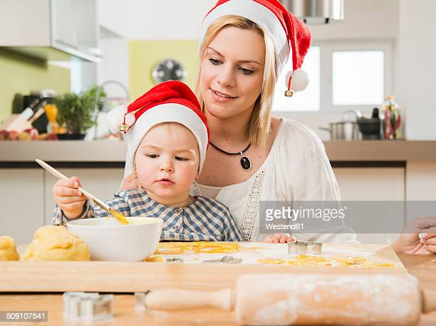 Mother and daughter wearing Santa hats baking in kitchen