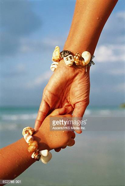 Mother and daughter (4-6) wearing shell braclets, holding hands