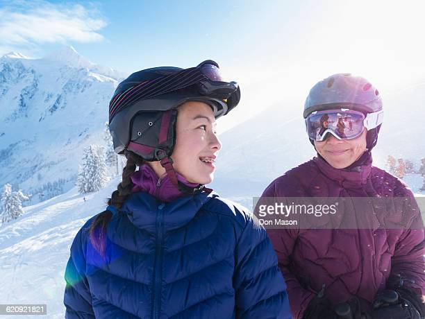 Mother and daughter wearing ski gear on snowy mountain