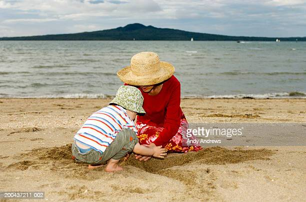 Mother and daughter (2-4) wearing sun hats playing in sand on beach