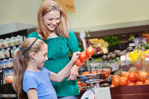 Mother and daughter weighing vegetables at the grocery store