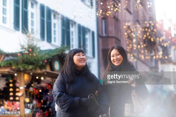 mother and daughter window shopping at christmas market, freiburg, baden-wurttemberg, germany - sigrid gombert stock-fotos und bilder