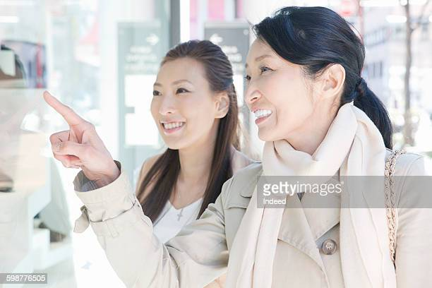mother and daughter window shopping - トレンチコート ストックフォトと画像