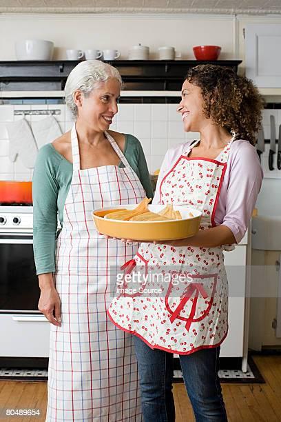 Una madre y su hija con un plato de tamales