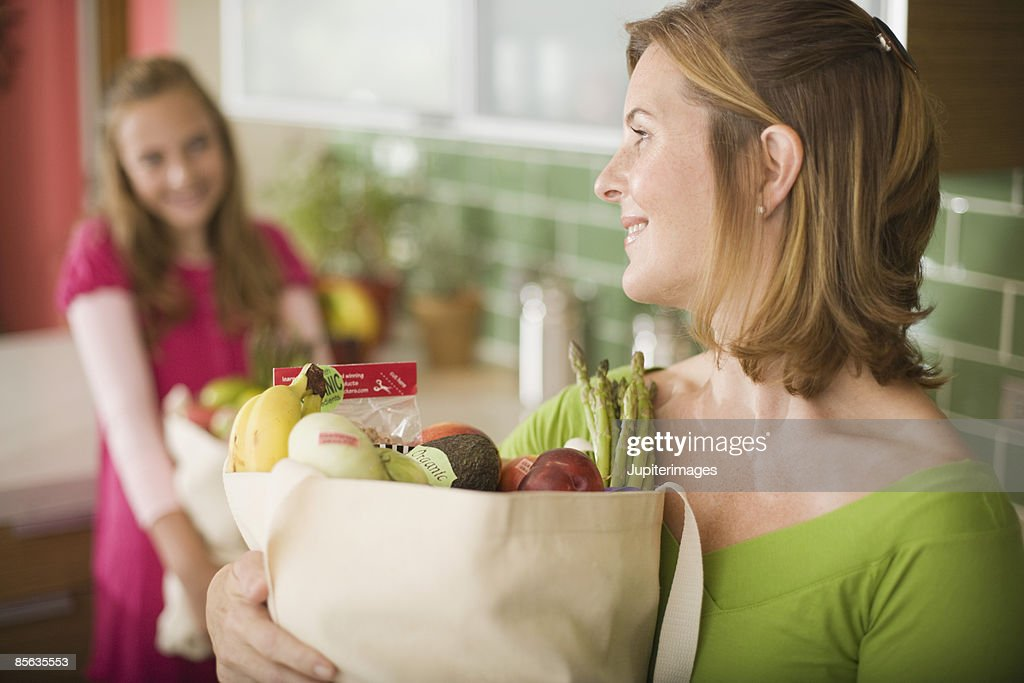 Mother and daughter with bags of fruits and vegetables : Stock-Foto