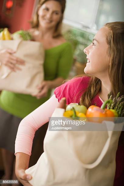 Mother and daughter with bags of fruits and vegetables