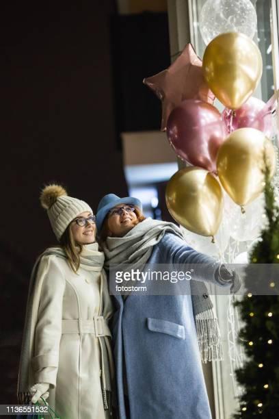 店の窓の前に風船を持つ母と娘
