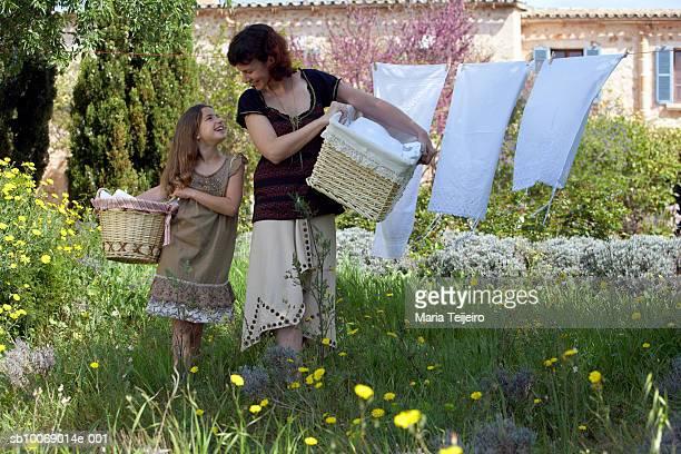 Mutter und Tochter (8.) mit Körbe im inneren Garten