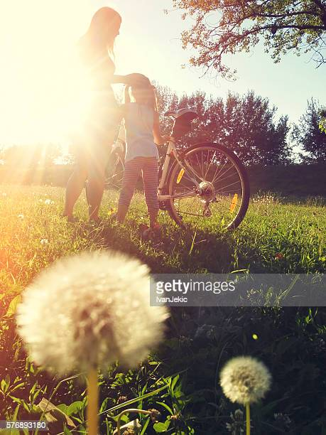Mother and daughter with bicycle in nature at sunset