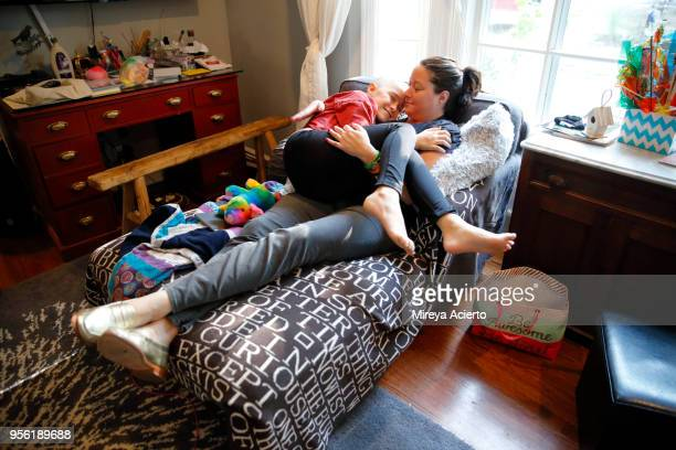 a mother and daughter with cancer happily embrace one another on the couch, in the living room. - ann arbor stock pictures, royalty-free photos & images