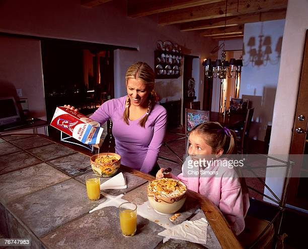 mother and daughter with cereal and spilled milk - milk carton stock photos and pictures