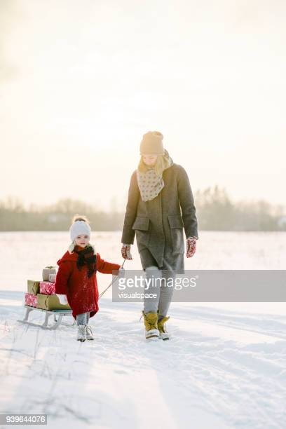 mother and daughter with christmas presents in the sunset - red coat stock pictures, royalty-free photos & images