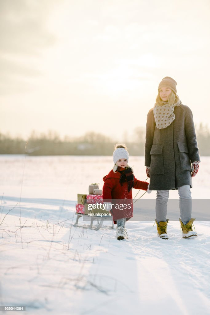Mother and daughter with christmas presents in the sunset : Stock Photo