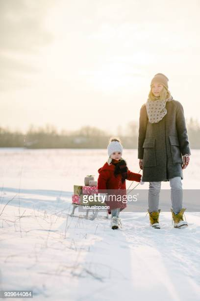 mother and daughter with christmas presents in the sunset - country christmas stock pictures, royalty-free photos & images