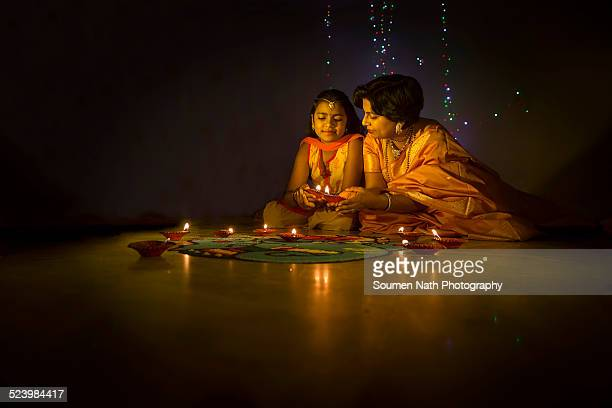 mother and daughter with diyas on diwali - diwali celebration stock photos and pictures
