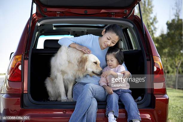 Mother and daughter (2-3) with dog in back of SUV