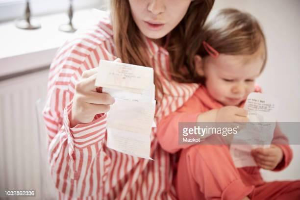 mother and daughter with financial bills at home - alleenstaande moeder stockfoto's en -beelden