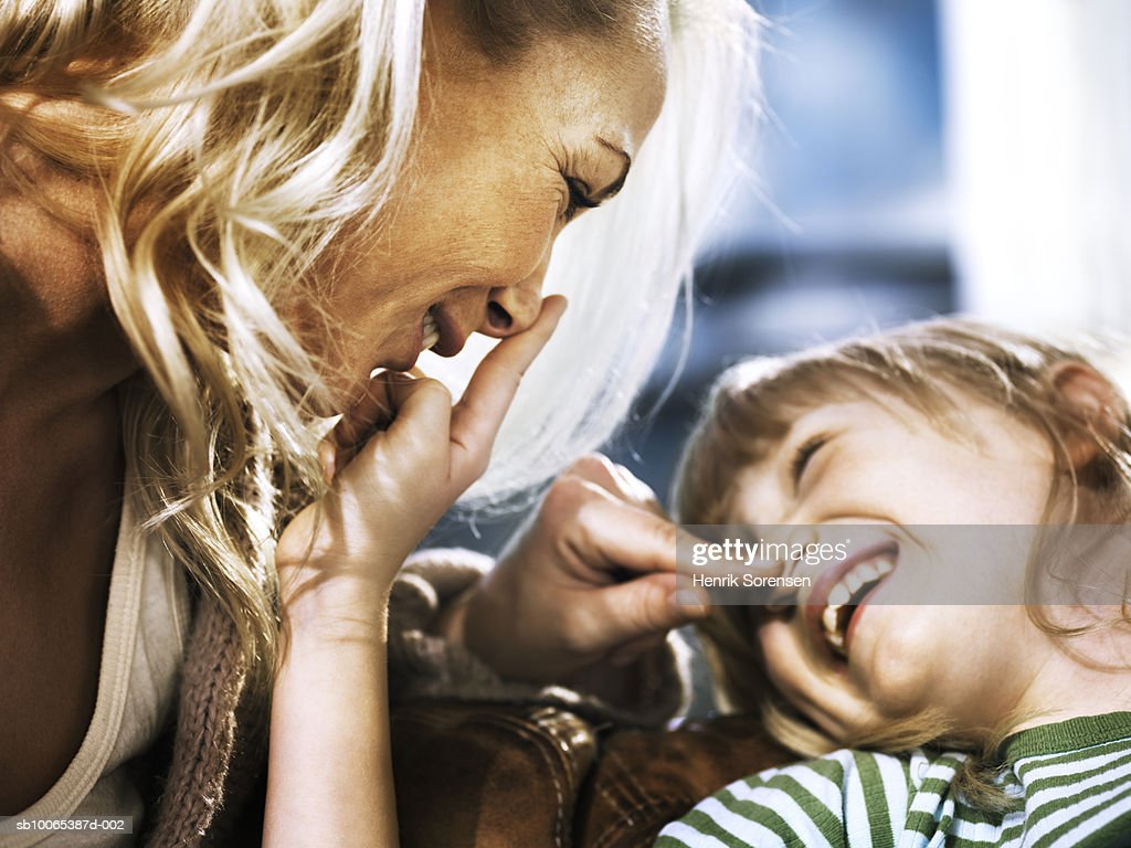 Mother and daughter (6-7) with fingers on each others noses, laughing : Foto stock