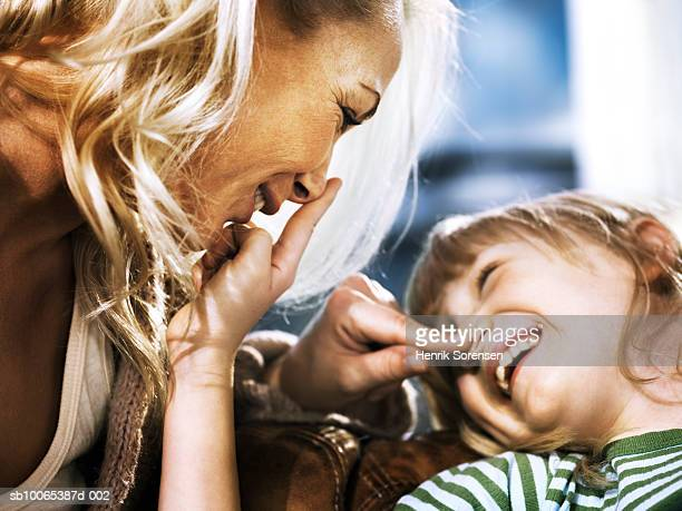 Mother and daughter (6-7) with fingers on each others noses, laughing