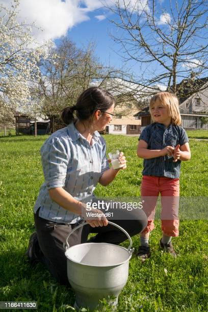 Mother and daughter with fresh milk in a bucket on pasture