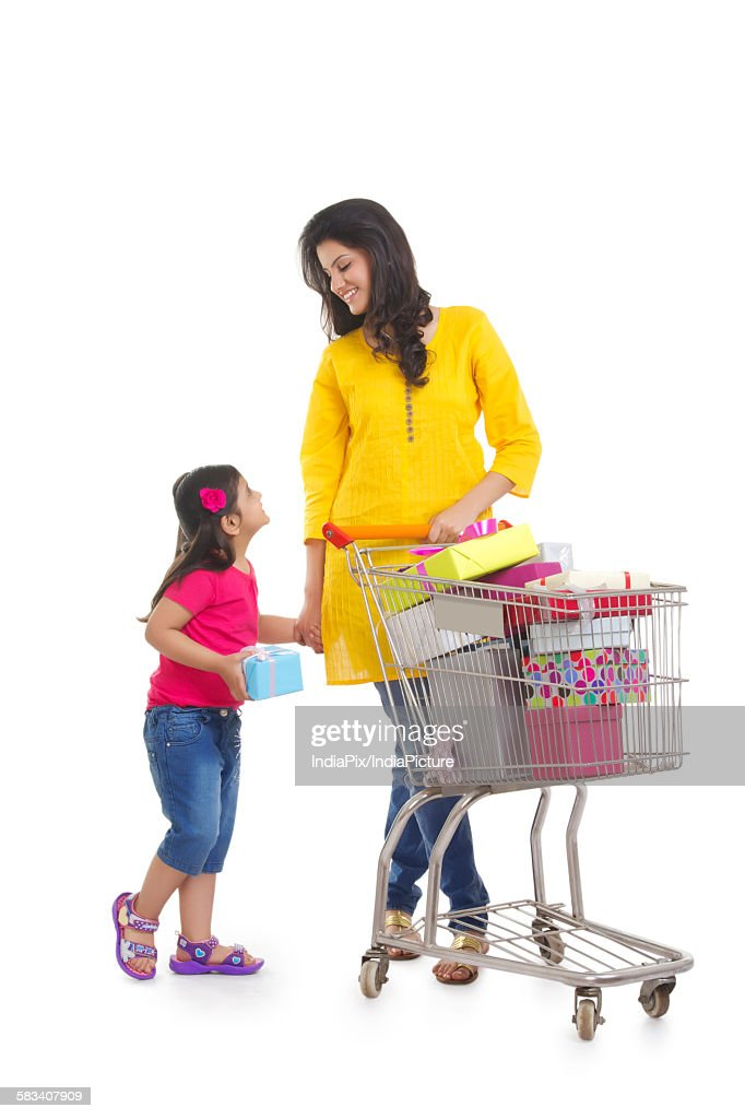 Mother and daughter with gifts in shopping cart : Stock Photo